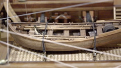 Miniature replica naval ship consisting of wood and thread with the boat on deck Stock Footage