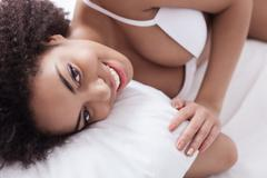 Attractive mulatto woman is relaxing at home - stock photo