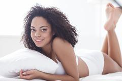 Cheerful mulatto woman is relaxing in bedroom Stock Photos