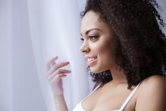 Cheerful mulatto woman is relaxing at home Stock Photos