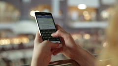 Woman uses a smartphone and write SMS in a shopping center Stock Footage