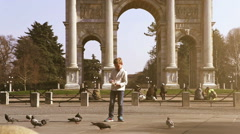Little boy feeding the pigeons on the Sempione Square in Milan with Porta Sempio Stock Footage