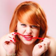 Redhair girl holding sweet food jelly candy on pink. - stock photo