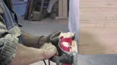 A man in a special uniform with his bare hands firmly holding an electric planer Stock Footage
