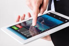Businessman using forex app on tablet Stock Photos