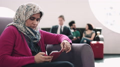 Woman with headscarf waiting in airport departure lounge on mobile phone Stock Footage
