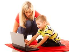 Technology and parenting - boy and mother with laptop - stock photo