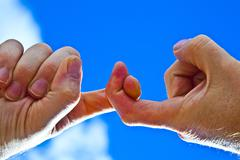 two fingers  with blue sky - stock photo