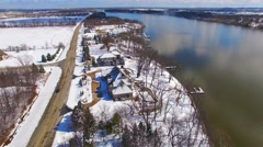 Stock Video Footage of Aerial view of wealthy riverfront homes covered in fresh snow