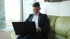 Businessman working at the laptop, rejoices and laughs, learning good news Stock Footage