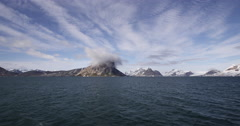Rocky arctic mountain range across sea with one gray cloud over peak Stock Footage