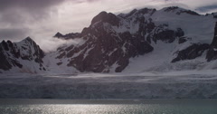 Sunlight glimmers on arctic sea at base of glaciers and mountains in clouds - stock footage