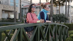 Two beautiful women standing on the bridge in the park and talking looking Stock Footage