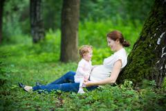 Young pregnant mother playing with her toddler daughter Stock Photos
