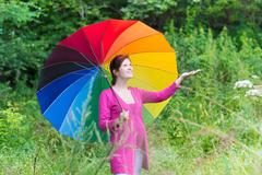 Young attractive pregnant woman walking under a colorful umbrella in the rain - stock photo