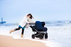 Beautiful young mother walking on a beach pushing an all terrain double stroller - stock photo