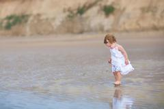 Beautiful little baby girl wearing a white dress walking on a beach Stock Photos
