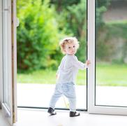 Adorable curly baby girl standing at a big glass door to the garden - stock photo