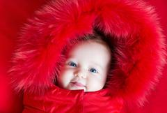 Cute funny baby girl with big blue eyes in a warm winter jacket with red hood Stock Photos