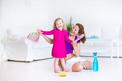 Mother and daughter sweeping the floor - stock photo