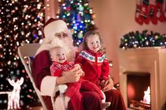 Kids and Santa at fire place on Christmas eve Stock Photos