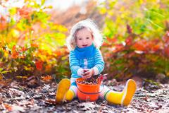 Little girl picking acorns in autumn park - stock photo