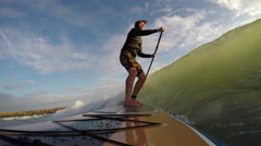 SUP (standup paddle board) surfing a wave Stock Footage