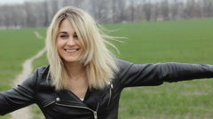 Portrait of young female rocker smiling and looking at camera at green field Stock Footage