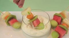 Dipping Fruit Kebabs In Yogurt Stock Footage