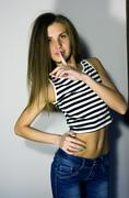 Sexy blonde girl in jeans and striped t-shirt puts a finger to her lips Stock Photos