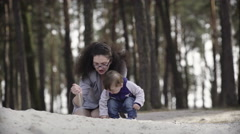 Mother with child playing with sand Stock Footage
