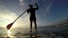 Stand up paddle board surfing at sunset Stock Footage