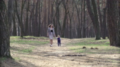Young mother on a walk in nature with her toddler son - stock footage