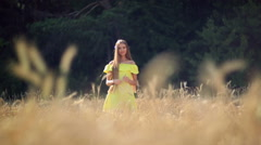 Beautiful girl with long hair walking between the ears of wheat. Stock Footage