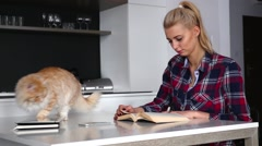 Young woman is reaking a book in the kitchen. Cat is walking on the table. Stock Footage