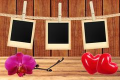 photo cards hanging on rope on clothespins, orchid and two red hearts over wo - stock photo