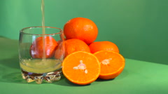 The juice is poured into a glass. Against the background of mandarin Stock Footage