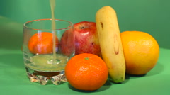 The juice is poured into a glass. the back of grapefruit, mandarin, banana,apple Stock Footage