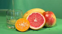 The juice is poured into a glass. back of grapefruit, mandarin, banana, apple Stock Footage