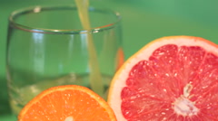 The juice is poured into a glass. background of cut grapefruit and tangerine Stock Footage