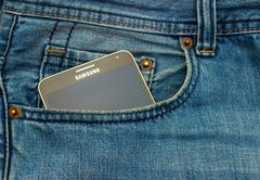 Modern SAMSUNG GALAXY NOTE in a denim pocket - stock photo