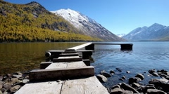 Wooden footbridge on Lower Multinskoe lake in the Altai Mountains - stock footage