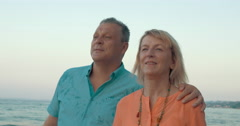 Couple of adults walking down the coastline - stock footage