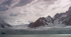 Slow pan of glacial bay with mountains in clouds reveals large ice cave Stock Footage