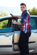 Modern dressed man standing near modern metalic car and holding key - stock photo