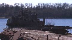Graveyard of ships on the river.  Many rusty barges and boats in water Stock Footage