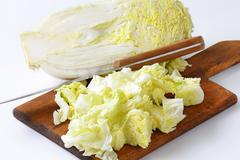 Chopped napa cabbage on cutting board Stock Photos