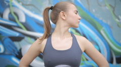 On graffiti background young athletic girl doing a workout before training Stock Footage