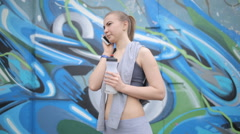 On graffiti background young athletic girl in a short vest talking on the phone Stock Footage