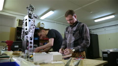 Two men repair the robot in the workshop Stock Footage